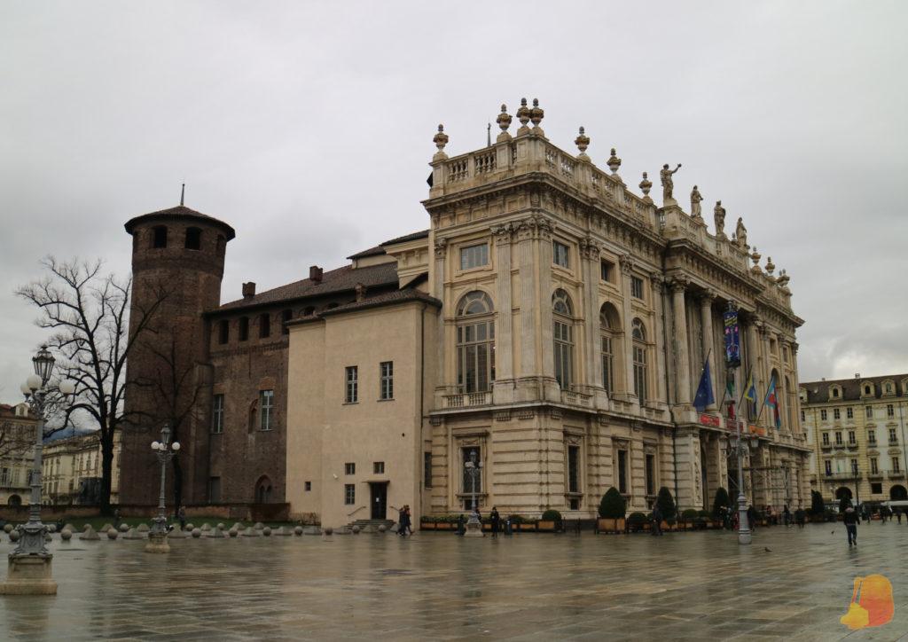 Fotografía tomada desde un lateral del Palazzo. La parte delantera es de color blanco y tiene estatuas sobre la fachada. La parte de atrás es de ladrillo y es mucho más sencilla.