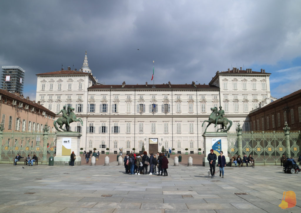 En primer plano se ve la puerta de acceso al Patio de Armas, con dos figuras ecuestres. Detrás se ve la fachada del Palacio de color blanco.