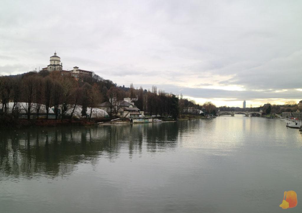 Se ve el río y junto a él la colina del monte dei Cappuccini y sobre ella una iglesia.