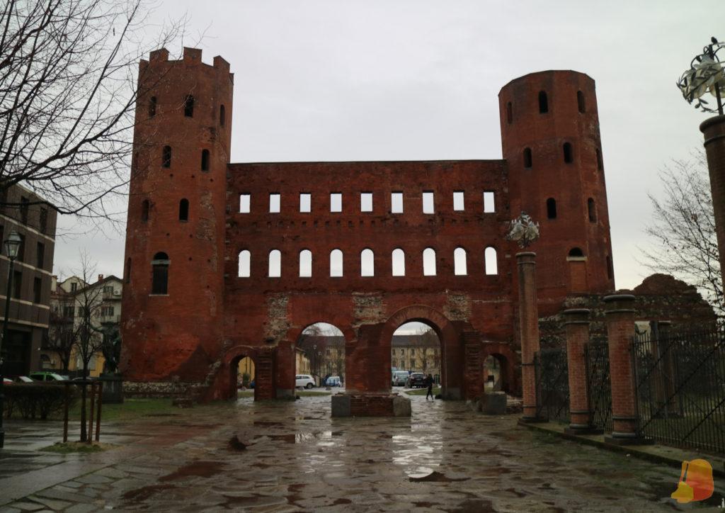 Puerta de ladrillo rojo con dos torres laterales y un cuerpo central de 20 metros de largo. La puerta tiene 4 aberturas, dos laterales para los peatones y dos centrales más grandes para los caballos.
