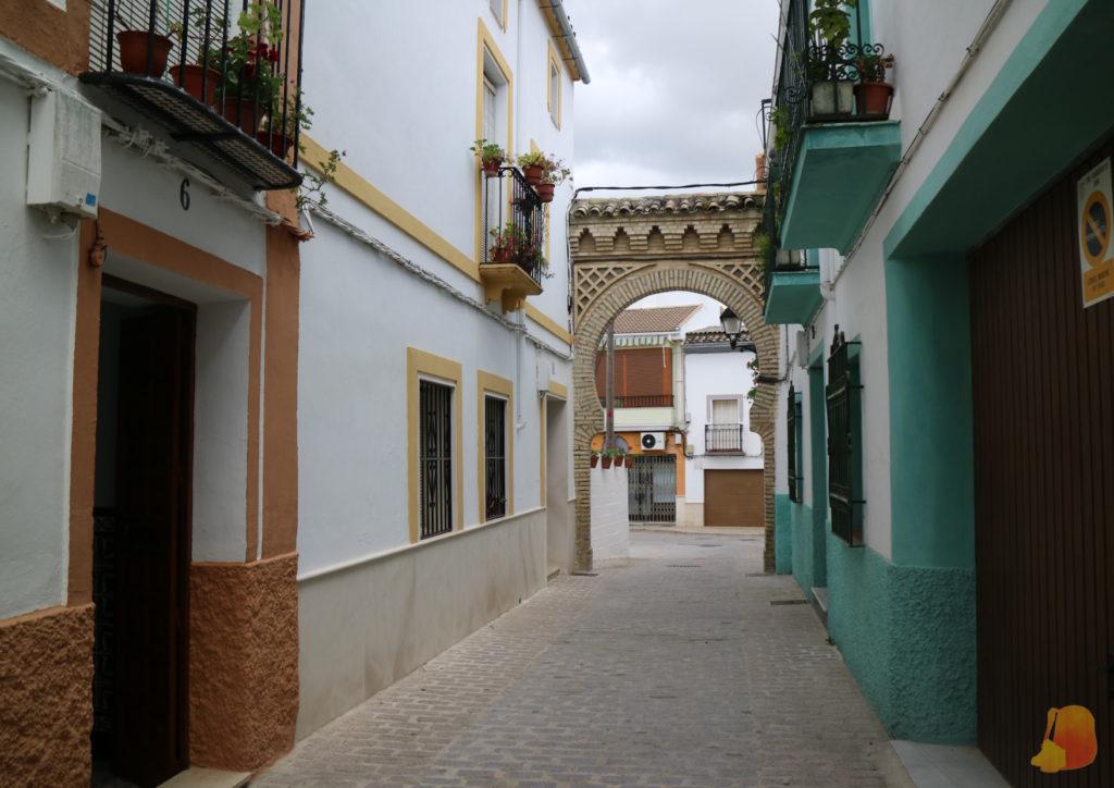 Calle estrecha con un arco de estilo árabe al final. Las casas de los lados son blancas con detalles en naranja (casa de la izquierda) y azul (casa de la derecha) y con balcones decorados con plantas.