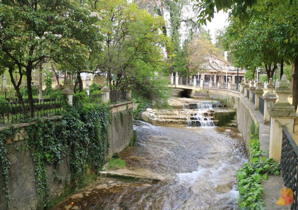 Parque con árboles y en el centro un canal por el que pasa el río Cabra