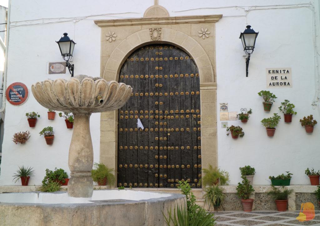 Fachada de la Ermita de la Aurora. Hay macetas colgadas a ambos lados de una gran puerta de madera con jamba de piedra. Delante una fuente.