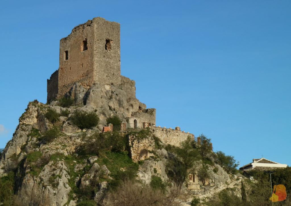 Torre y restos de un castillo que se alzan sobre un roquedo natural.