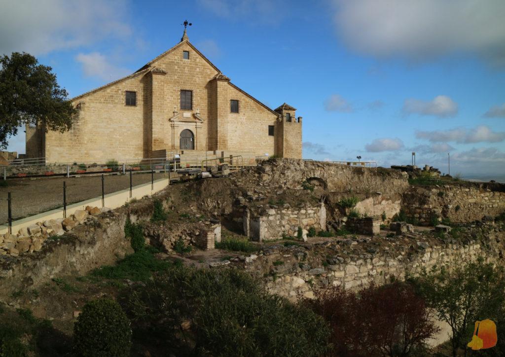 Se ven los restos arqueológicos y sobre ellas la pasarela y un edificio de piedra que funciona de graneros.
