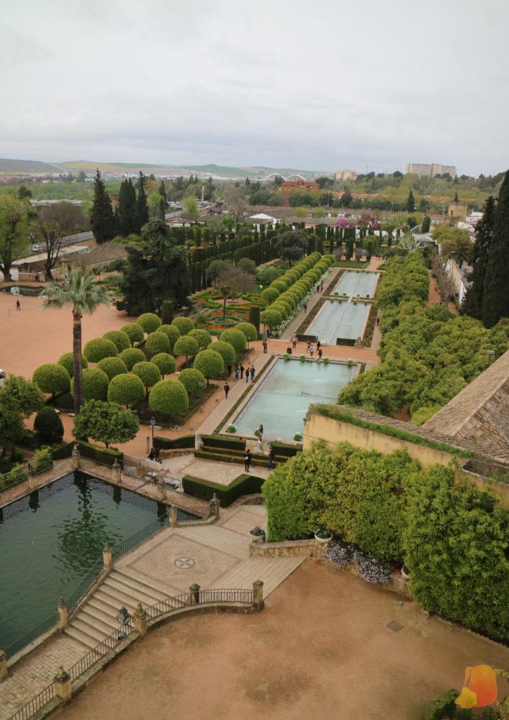 Se ven los jardines del Alcazar. Los arboles se reparten en torno a las diferentes piletas de agua rectangulares.
