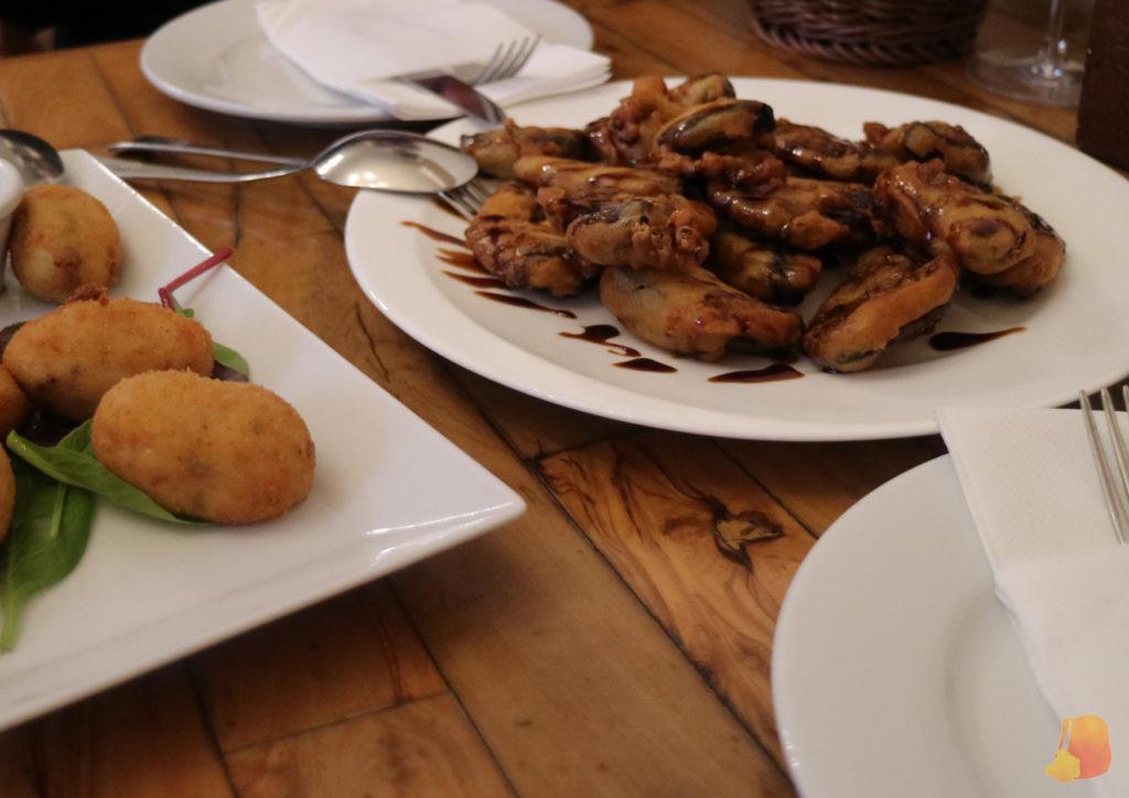 Plato de berenjenas rebozadas y fritas con miel por encima y plato de croquetas.