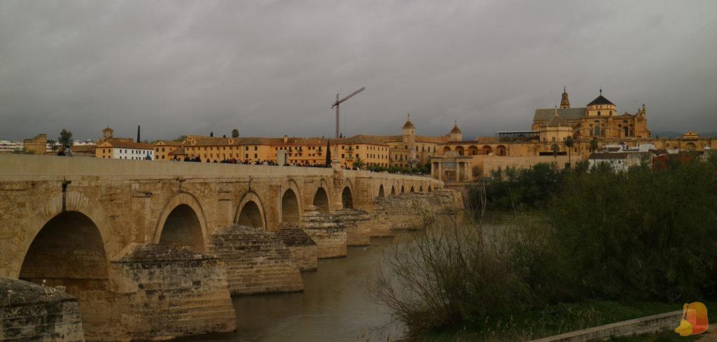 En primer plano se ve el Puente Romano de Córdoba bajo el cual fluye el Guadalquivir. De fondo se ve la cúpula de la Catedral