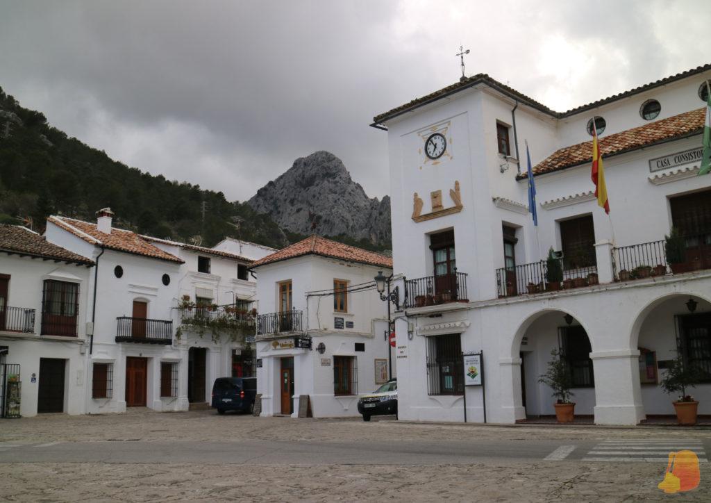 Se ve la esquina de la plaza con las fachadas blancas y parte del Ayuntamiento. Al fondo un gran roquedo.