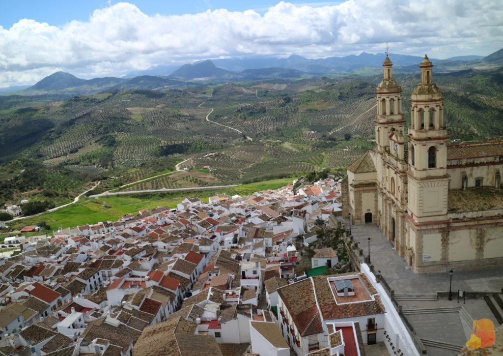 A la derecha la Iglesia y bajo ella se extiende el pueblo. De fondo se ven las montañas de la Sierra de Grazalema.