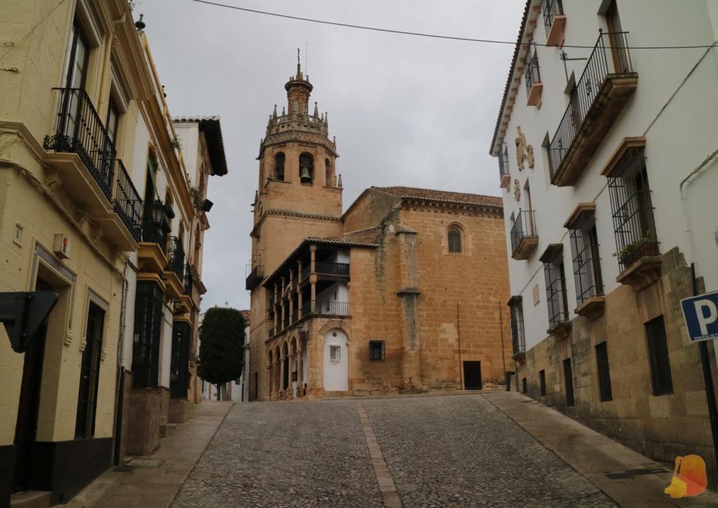 Al fondo de una calle que sube se ve la Iglesia con su campanario. La fachada que da a la plaza tiene un pórtico en dos alturas
