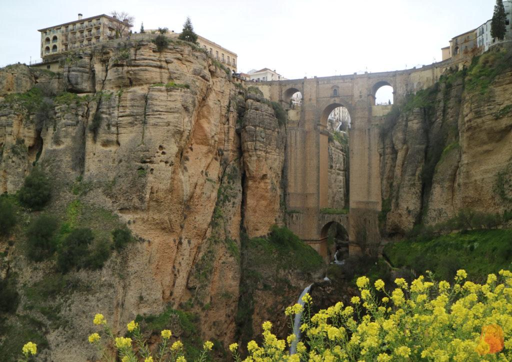 El Puente Nuevo visto desde abajo. Se percibe mejor la altura del puente y debajo el río forma una pequeña cascada en su descenso hasta el fondo del desfiladero