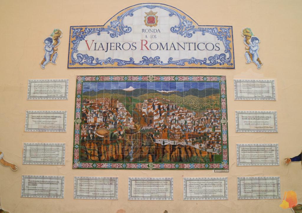 """Gran mural con cerámicas decoradas. La de arriba pone """"Ronda a los Viajeros Romanticos"""". La central es una panoramica de la ciudad. En torno a esta última hay once cerámicas mas pequeñas con citas escritas"""