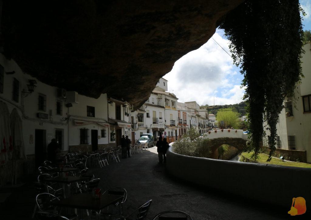 Se ven las fachadas encajadas en la roca. Una parte de la roca hace de visera dando sombre a parte de las casas. Paralelo a la calle fluye un riachuelo.