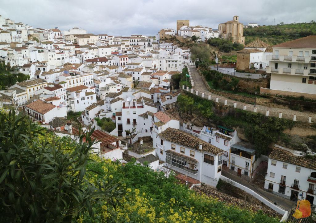 Las casas están escalonadas en el terreno. Se ve la fachada de la casa encajada en la roca. En el punto más alto se alza la Torre del Homenaje y la Iglesia