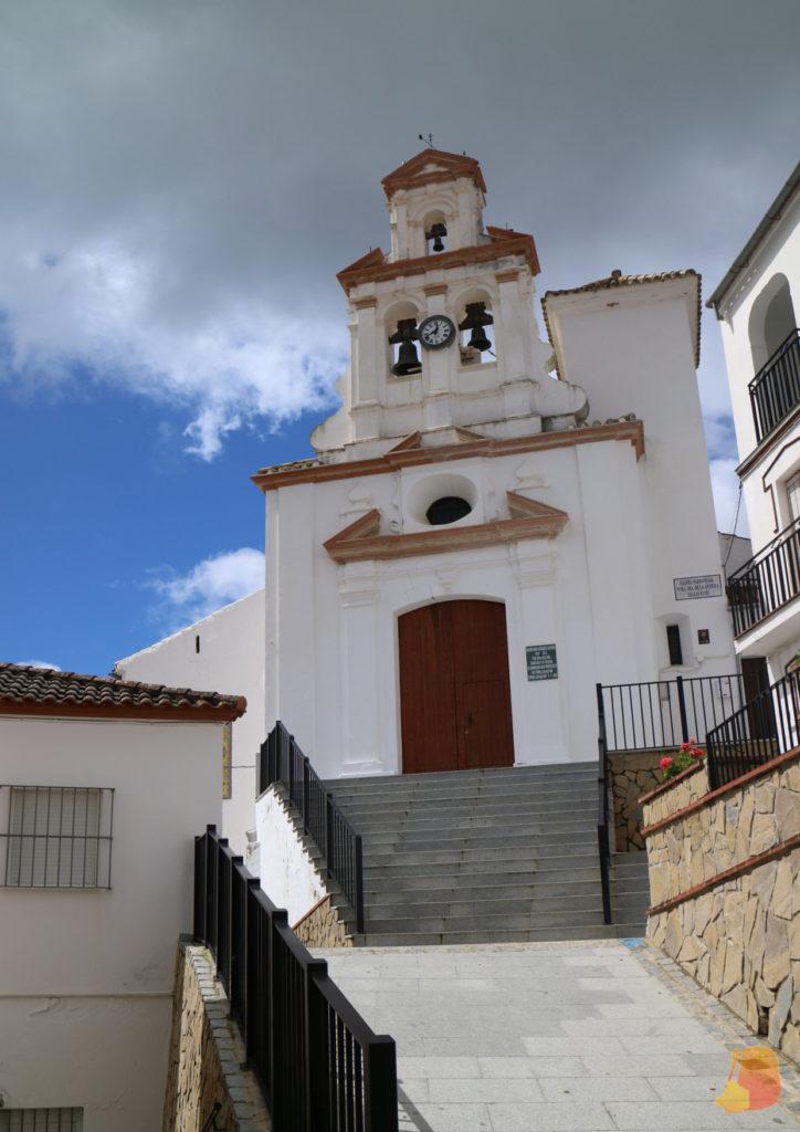 Una rampa y unas escaleras ascienden hasta una pequeña iglesia de paredes blancas.