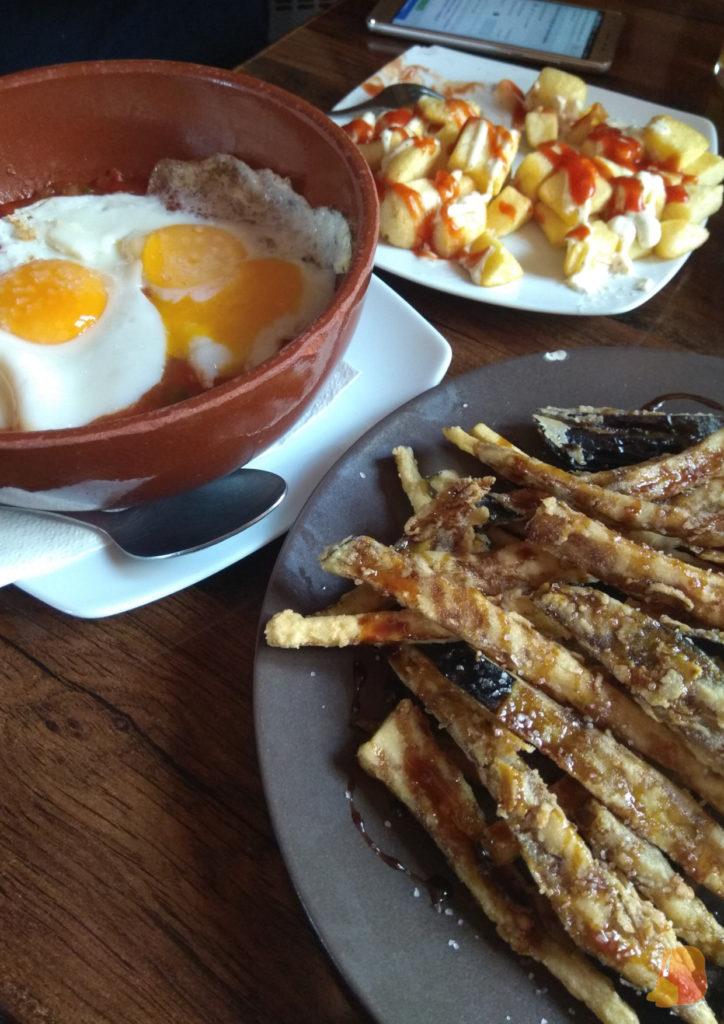 Se ven tres platos: patatas bravas, pisto con huevo y berenjenas fritas con miel