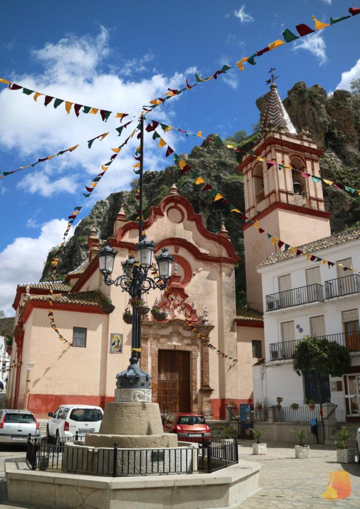 Se ve la fachada de la iglesia, de color beige y rojo. La plaza está decorada con banderines.