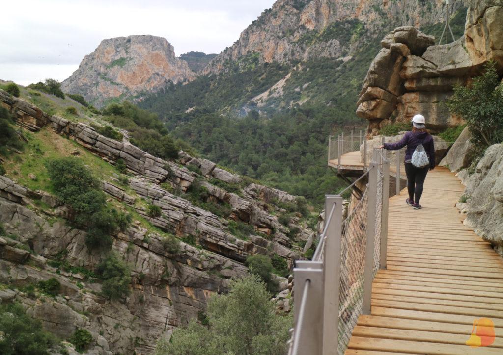 Yo de espaldas avanzando por la pasarela. El paisaje son las paredes del desfiladero.