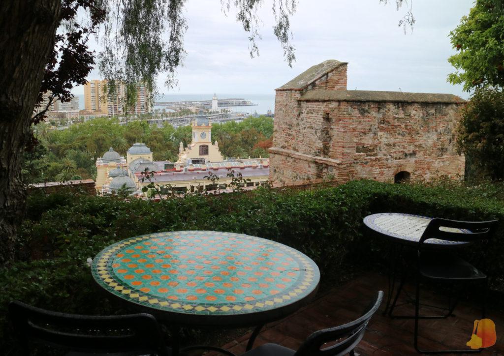 En primer plano dos mesas de mosaico de la cafetería de la Alcazaba y de fondo las vistas