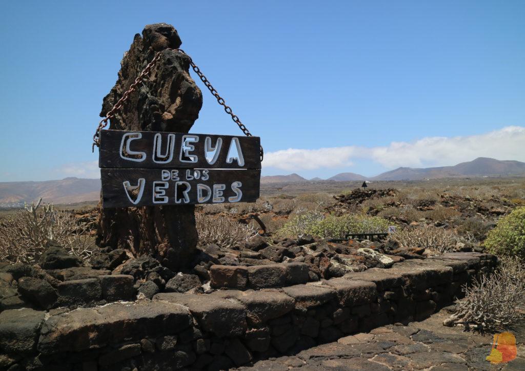 Cartel que pone Cueva de los Verdes. El cartel cuelga de una roca volcánica