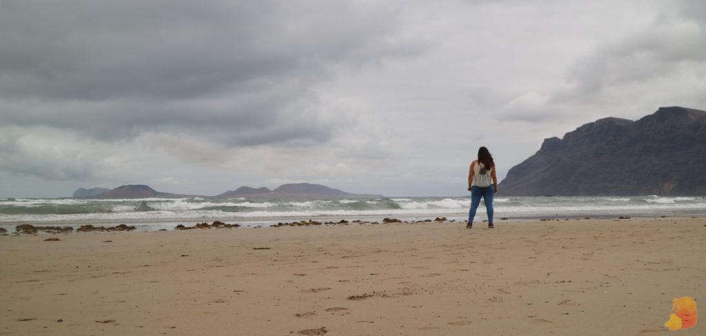 Playa de Arena con vistas a un barranco y a una isla. Yo de espaldas a la camara cerca de la orilla