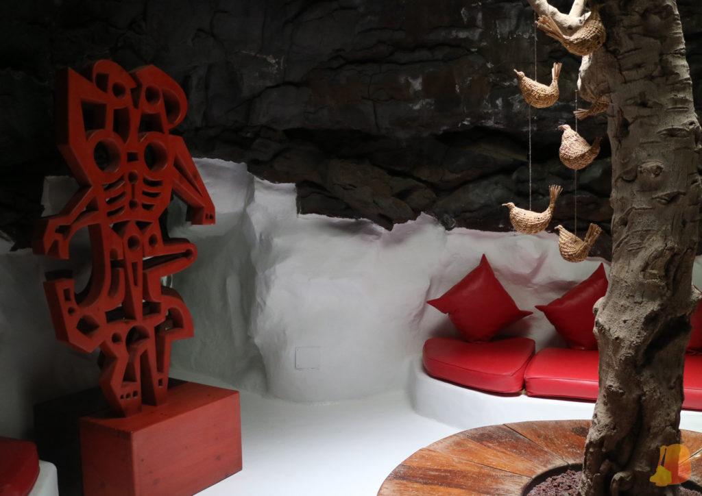 La mitad inferior de las paredes está encalada y el resto es de piedra volcánica. Hay una escultura rojo y un banco con cojines del mismo color