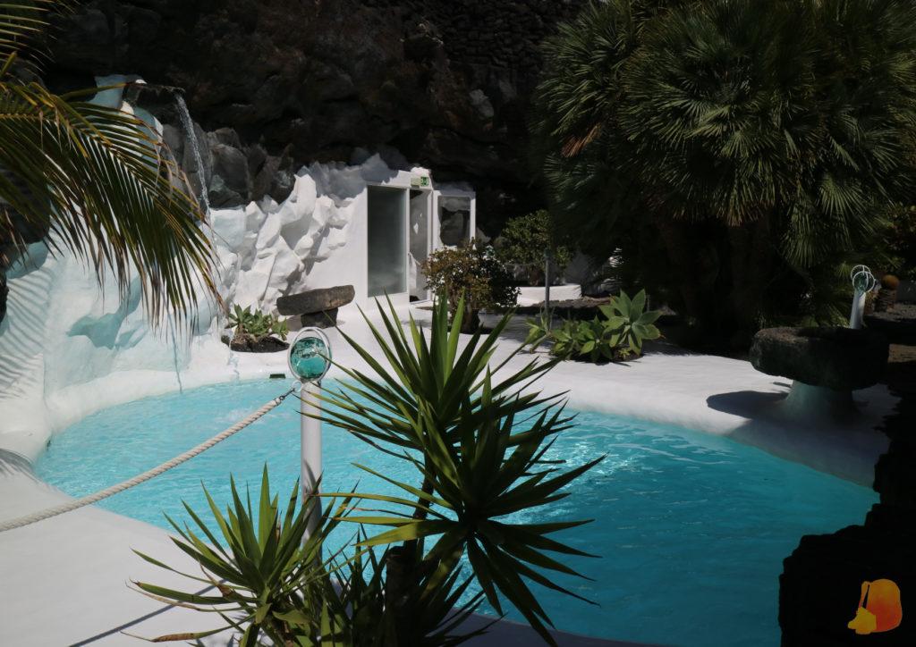 Piscina rodeada de pequeñas palmeras. El suelo esta encalado y el agua es de color turquesa