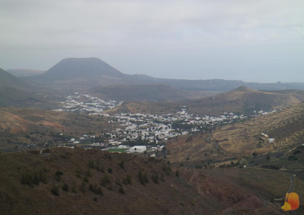 Vistas del pueblo desde las alturas. Al fondo se ve el Volcán de la corona. Las casas blancas destacan sobre la tierra de tonos marrones y negros
