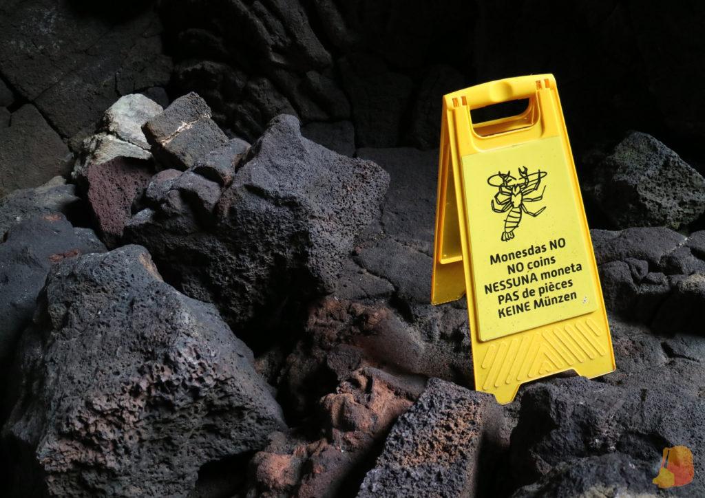"""Cartel amarillo que pone """"Monedas no"""" colocado sobre las rocas volcanicas"""