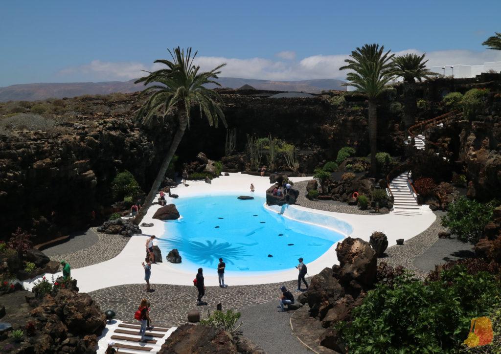 Se ve el interior del Jameo principal con una piscina central rodeada de palmeras