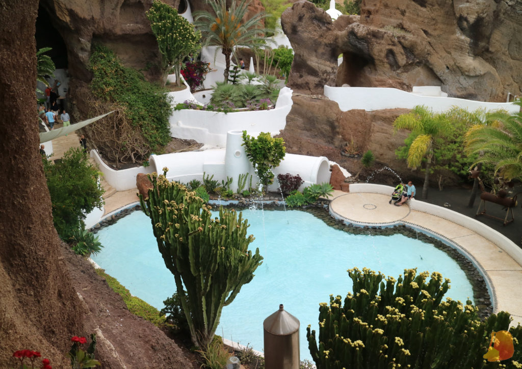 Se ve una piscina central y como el resto de las habitaciones se van metiendo en la piedra marron de la montaña