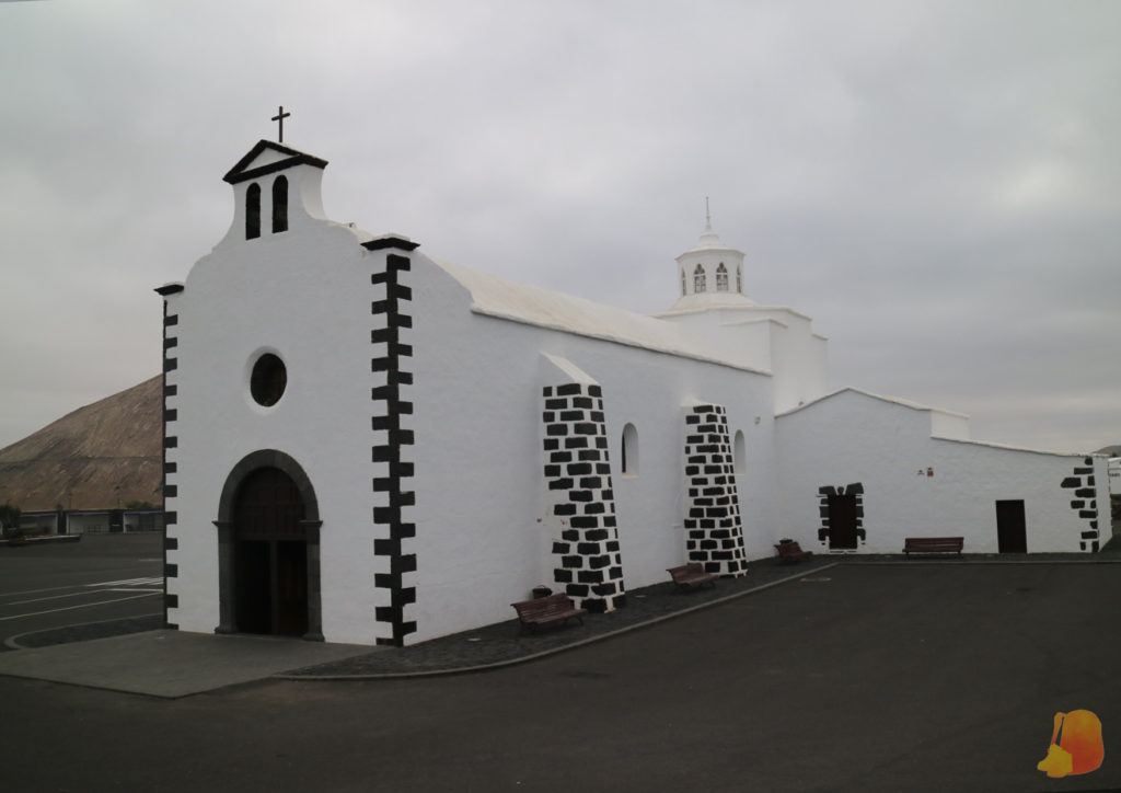 Iglesia de paredes encaladas de blanco y decorada con piedras negras