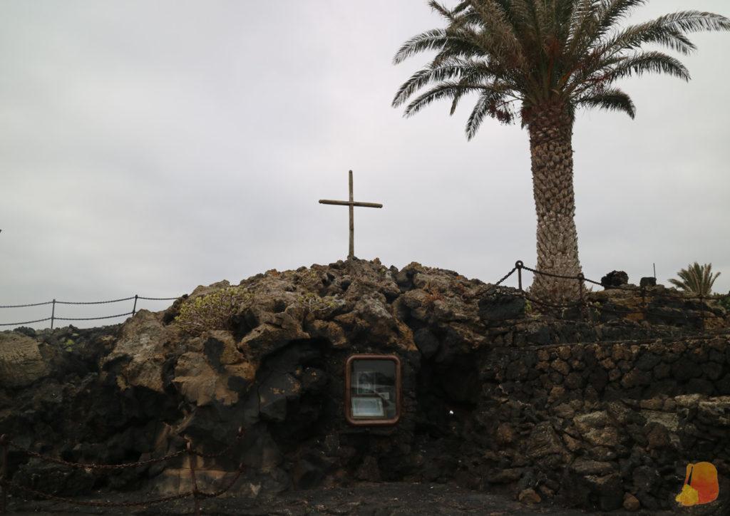 Una cruz de madera sobre los restos del malpais. Bajo la cruz hay un pequeño altar.