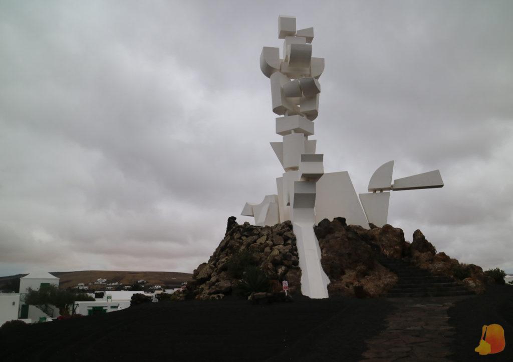 Monumento hecho con grandes piezas blancas y que forma la silueta de un campesino y su perro