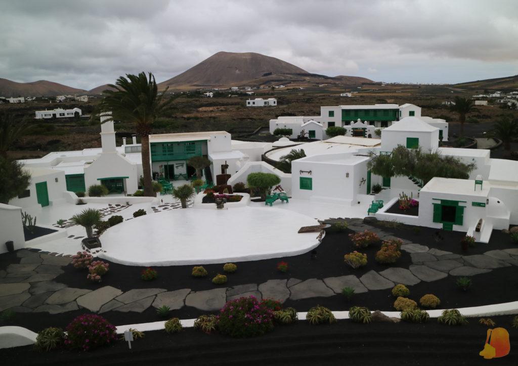 Destacan las casas en blanco sobre la tierra negra. Los balcones, las ventanas y las puertas son verdes.