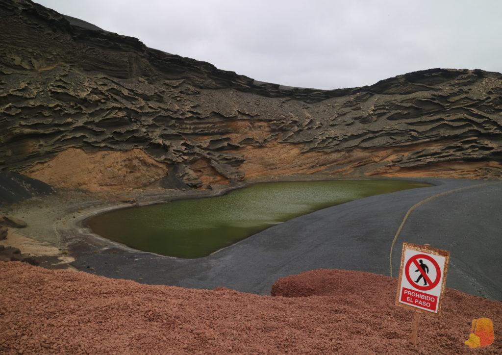 Se ve el lago con agua de color verde y la arena negra de la playa