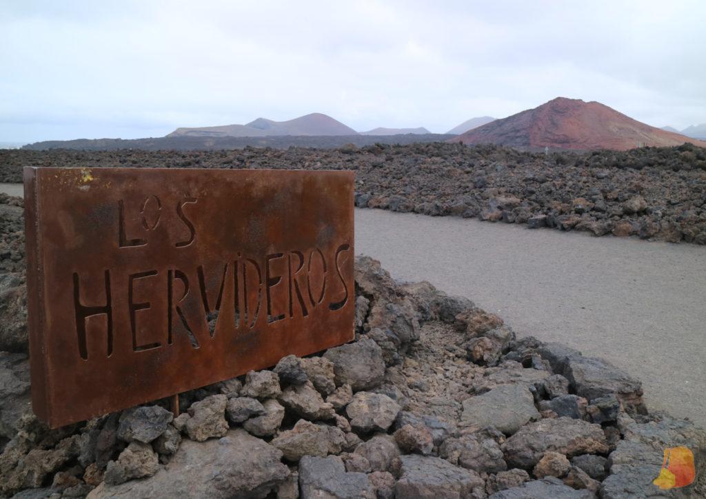 """Cartel de acero corten en el que se lee """"Los Hervideros"""". De fondo la montaña de arena roja y negra"""