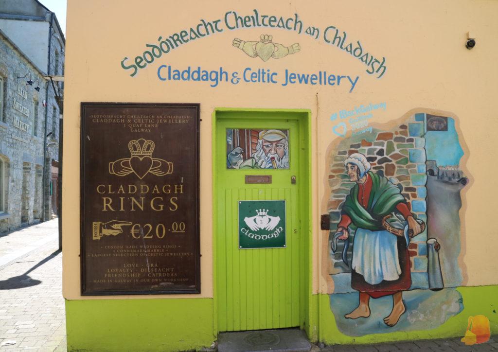 Anuncio de los anillos de Claddagh junto a un mural pintado en la pared