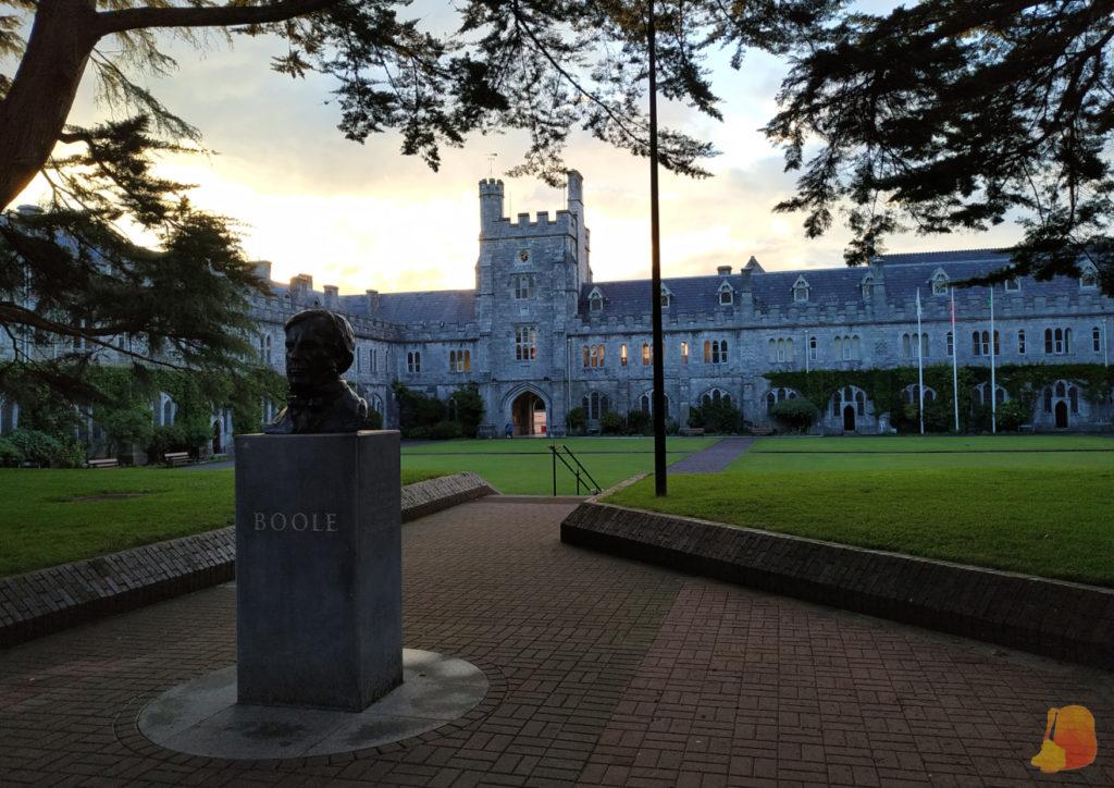 En primer plano, busto de Boole y detrás, el edificio principal de la UCC