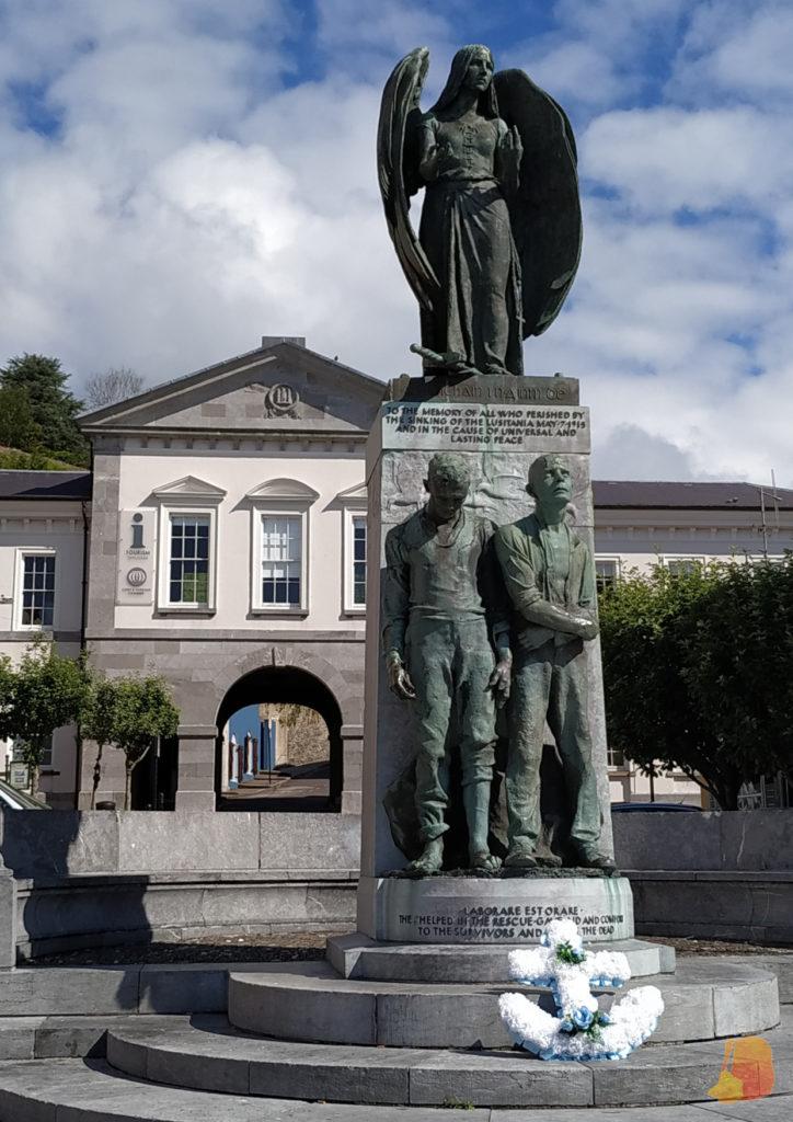 Monumento coronado con un Angel y, bajo el, dos pasajeros de pie