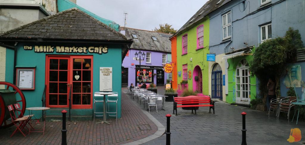 Calle peatonal con una terraza, negocios de diferentes colores y un banco rojo en el centro de la imagen
