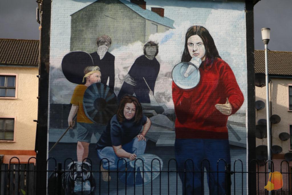 En el mural aparece una chica joven con un megafono y un grupo de jovenes detrás con tapas de cubos de basura y palos