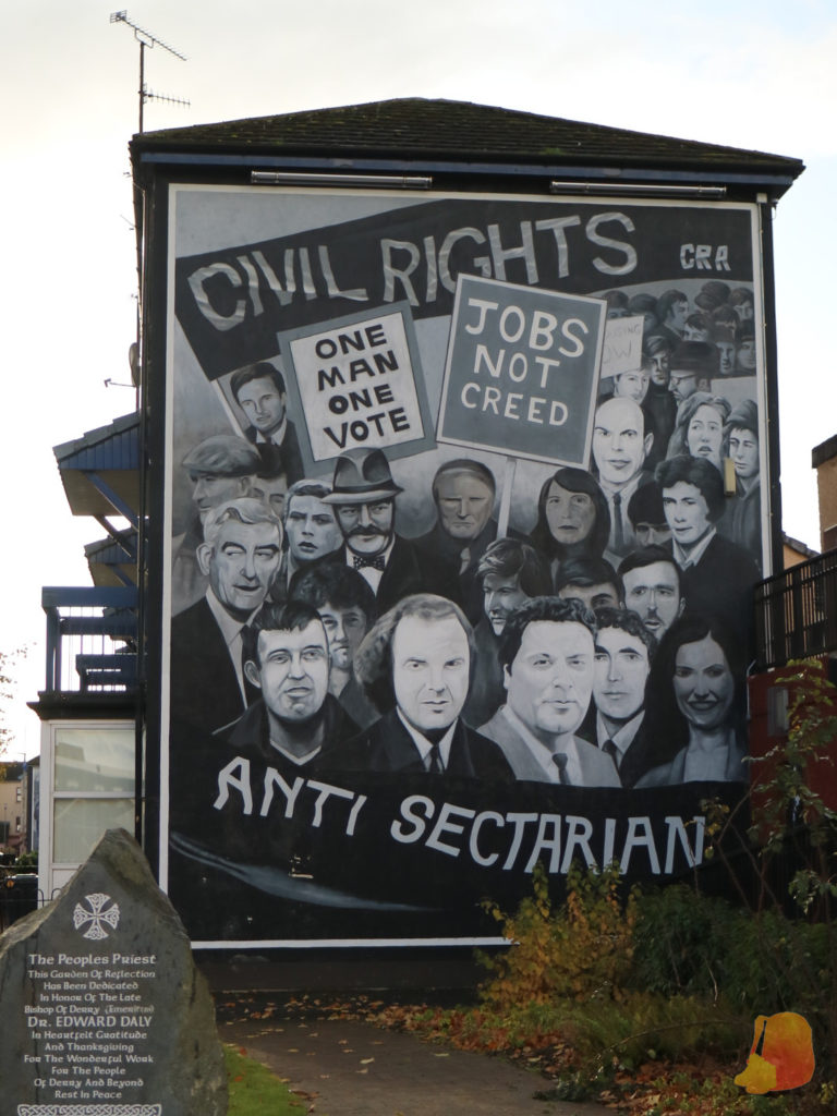 """Mural en el que aparece representada una manifestacion. Las pancartas rezan """"One man, one vote"""" y """"Jobs not creed"""""""