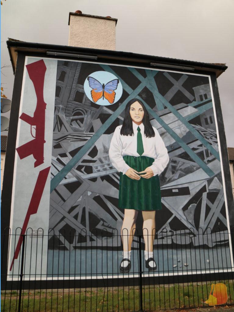 En este mural aparece una niña vestida con su uniforme del colegio. También aparece una mariposa que simboliza la inocencia y una escopeta rota por la mitad