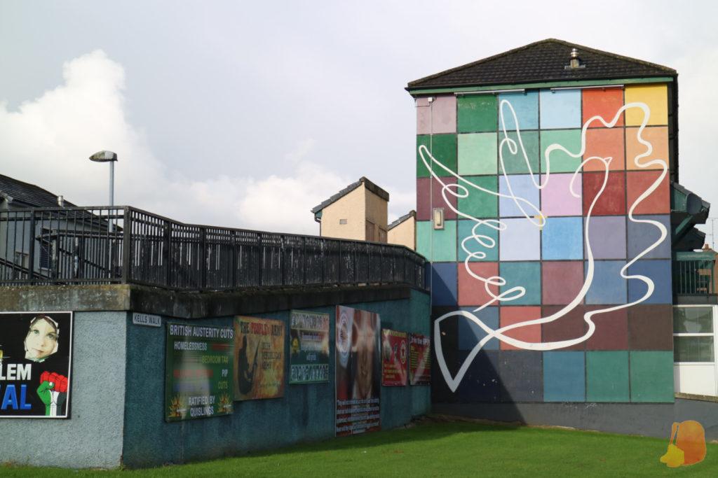 En el mural aparece la silueta de una paloma sobre un fondo de cuadrados de colores