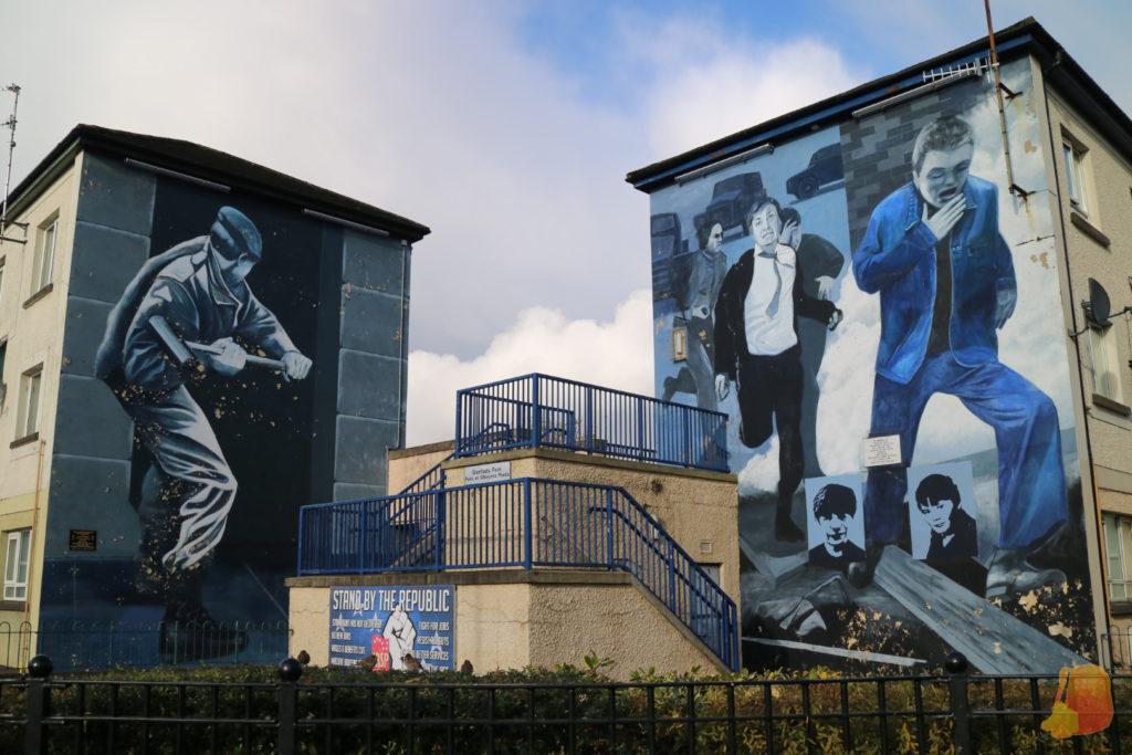 Aparecen dos murales de Free Derry. En el de la izquierda aparece un soldado echando abajo una puerta con un mazo. En el de la derecha aparecen personas huyendo de los ataques