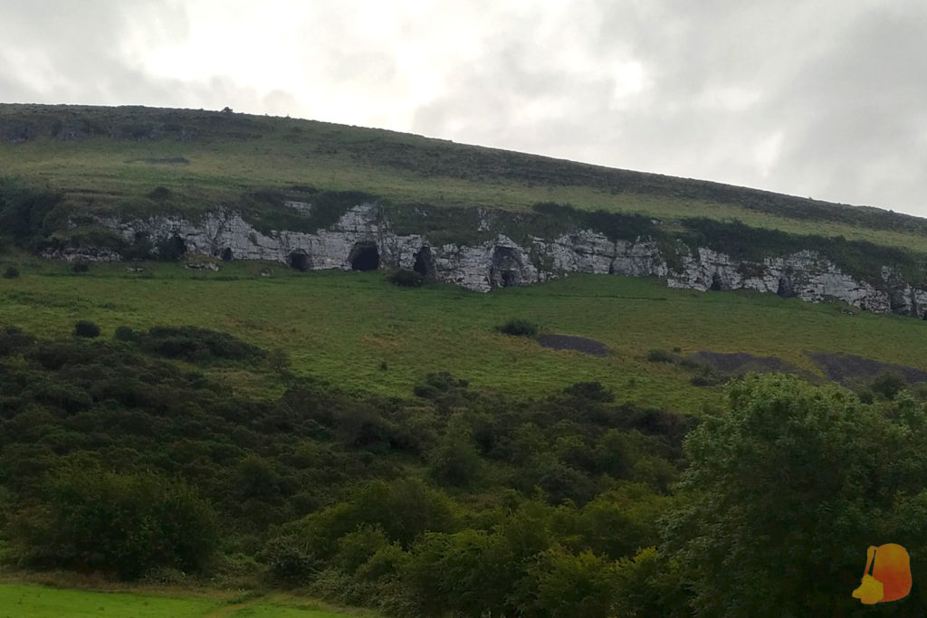 Las cuevas vistas desde la base. Se abren sobre la roca gris y el resto de la montaña es verde por la hierba