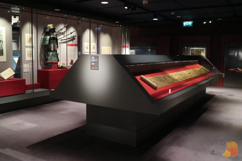 Vitrina con un pergamino y detrás una vitrina grande con una armadura samurai en la Chester Beatty Library en Dublin