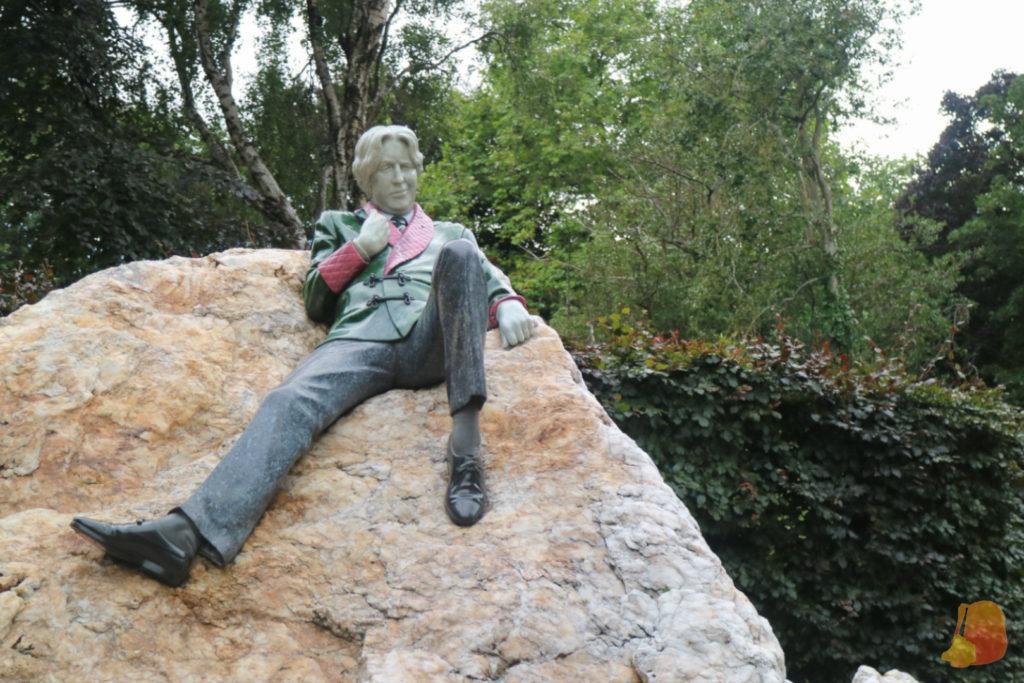 Escultura de Oscar Wilde recostado en una piedra